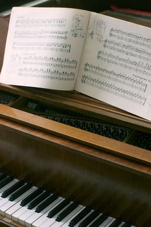Antique Piano with music notes book wide open photo