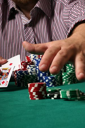 jack pot: Confident poker player showing big slick and grabbing the pot Editorial