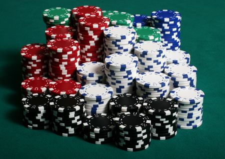 Large amount of poker chips stacked on a green felt pokertable photo