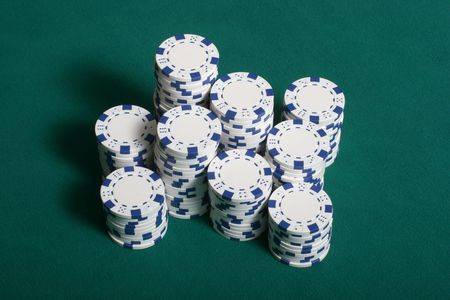 Poker chips stacked up on a green felt poker table photo