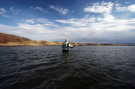 Flyfisherman casting in calm waters Stock Photo - 557270