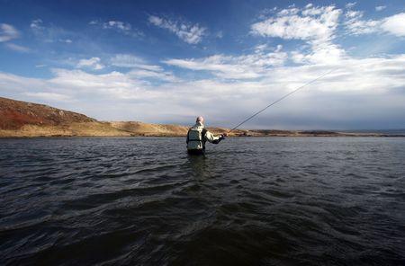 Flyfisherman odlewanie w spokojnych wodach