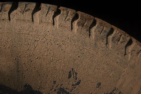 muddy tracks: Car tire covered in dirt and mud after driving offroads