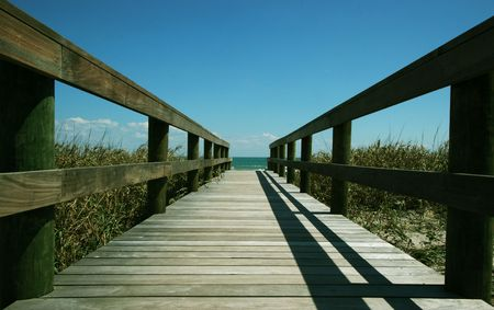 Wooden pathway leading down to a beautiful beach photo