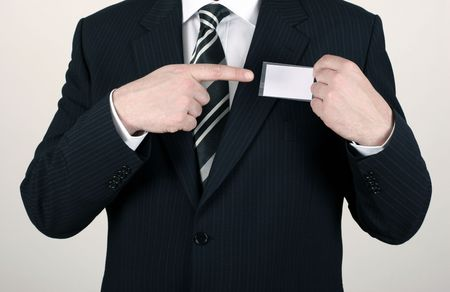 Business man wearing a suit pointing to a blank namebadge - insert your own brand and information photo