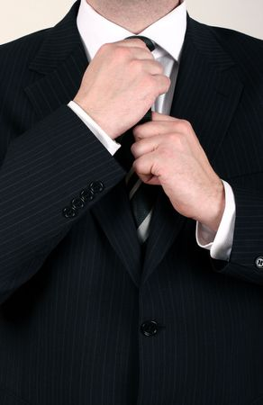 dresscode: Well dressed business man adjusting his tie for a meeting