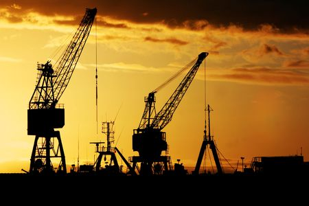 Industrial dock at early dawn - Silhouette of cranes and ships