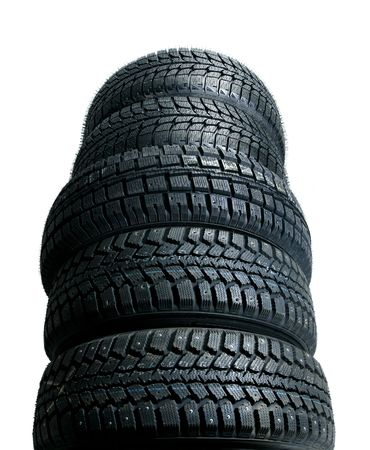 Brand new tires stacked up and isolated on white background - worms view photo