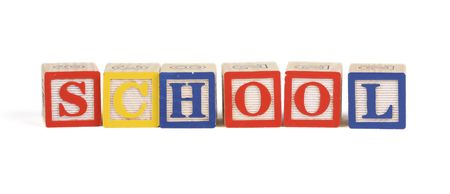 Alphabet blocks lined up to spell School - isolated on white photo
