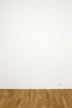Blank white wall in a clean room with wooden floor - insert your own design on the wall