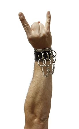 Rocker with a leather bracelet raising his hand with a rock and roll sign Stock Photo