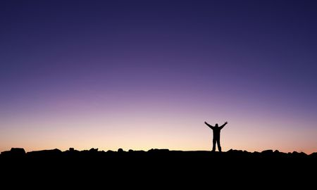 Silhouette of a man raising his hands into the sunrise after conquering a summit photo