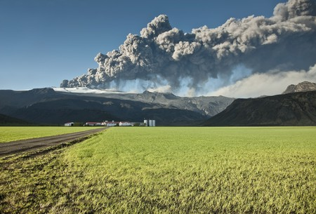 Ash cloud from the Eyjafjallajokull eruption in Iceland towering over a nearby farm Stock Photo