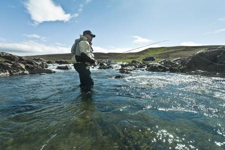 waders: Pescador con mosca fundici�n la mosca en el hermoso entorno de Islandia