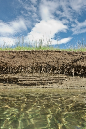 rock layers: Riverbank on a clear day showing cross section of the earth with roots and layers of dirt Stock Photo