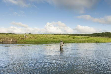 Man fishing for salmon in a beautiful surrounding photo