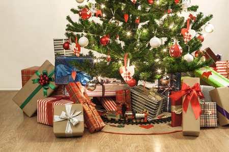 beautifully decorated christmas tree with a toy train and lots of presents Фото со стока