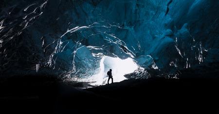 Man het verkennen van een verbazende ijzige grot in IJsland Stockfoto