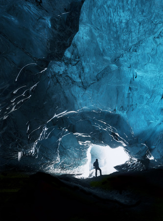 discoverer: Man exploring an amazing glacial cave in Iceland