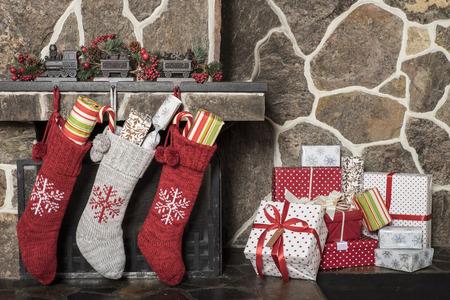 Gefüllte Strümpfe hängen an einem Kamin auf Weihnachtsmorgen