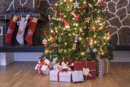 Medias que cuelgan en una chimenea al lado de un árbol de Navidad en la mañana de Navidad Foto de archivo