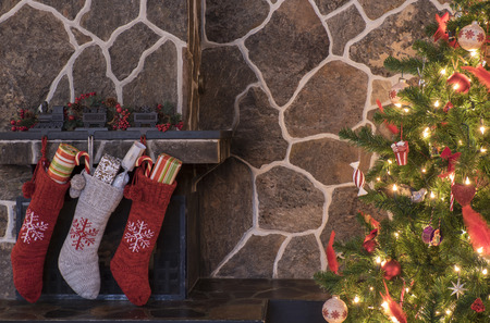 Stockings hanging on a fireplace next to a christmas tree on christmas morning Stockfoto