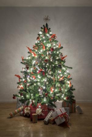 christmas tree ornament: Beautiful illuminated christmas tree in a living room