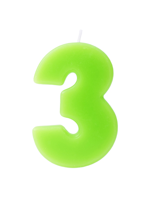 third age: Green birthday candle in the form of the number three on white background