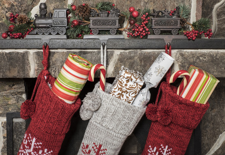 morning: Stuffed stockings hanging on a fireplace on christmas morning