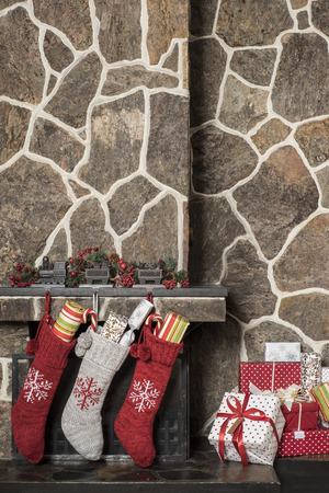 giftwrapped: Stuffed stockings hanging on a fireplace on christmas morning