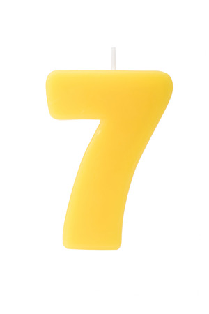 number seven: Yelllow birthday candle in the form of the number seven on white background