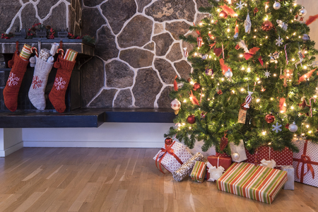 Stockings hanging on a fireplace next to a christmas tree on christmas morning Stock Photo