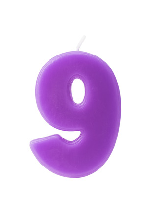 nine years old: Purple birthday candle in the form of the number nine on white background Stock Photo