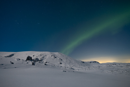 snow covered mountains: Northern lights in the sky over snow covered mountains Stock Photo