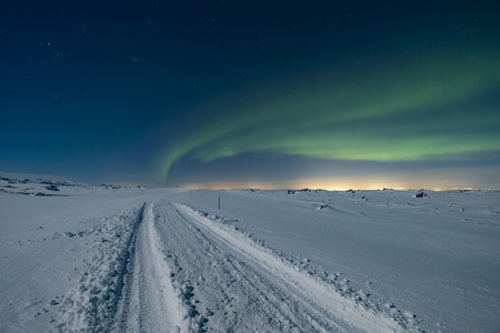 The northern lights dancing in the sky above a frozen mountain road Stock Photo