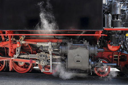 railway transportation: Vintage steam train leaving the station Stock Photo