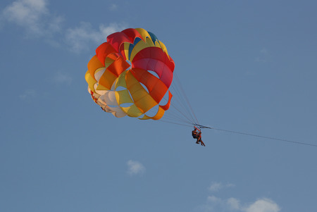Two People are Flying in the Blue Sky Using a Colorful Parachute.