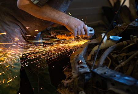 The Employee of The Car Service Station Produces Body Repair with a Welding Machine in Hand. Sparks From Welding Machine.