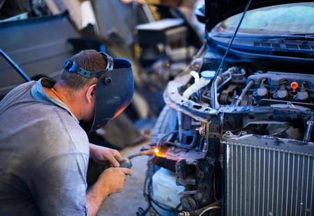 Welding industrial: worker in helmet repair detail in car auto service Banco de Imagens