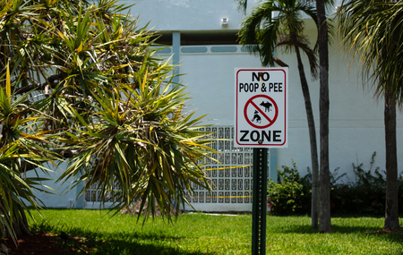 No dogs poop and pee zone sign. Red sign based near the house. Banco de Imagens