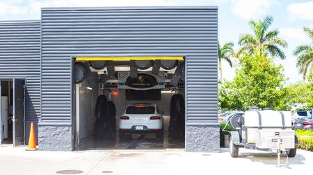 Miami, FL, USA - April 16, 2019: White car Porsche Macan on an automatic car wash. Special car wash Porsche only.