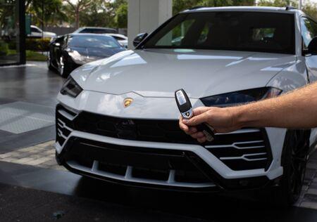 Miami, FL, USA - April 16, 2019:Male Hand Unlocks Luxury White Lamborghini Urus. The Lamborghini Urus is an SUV manufactured by Italian car manufacturer