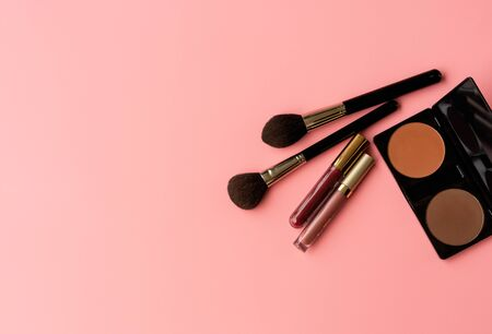 Set of professional cosmetic: make-up brushes, shadows, lipgloss on pink background. Overhead view. Copy Space for your text.