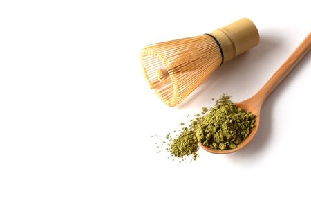 Wooden spoon full of Matcha Powder with a bamboo chasen (whisk)on a white Backgound. Japanese Culture. Tea Ceremony Concept. Copy Space Banco de Imagens