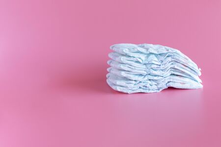 Stack of baby disposable diapers  on a Pink Background.  Baby Care Concept. Copy Space for Text
