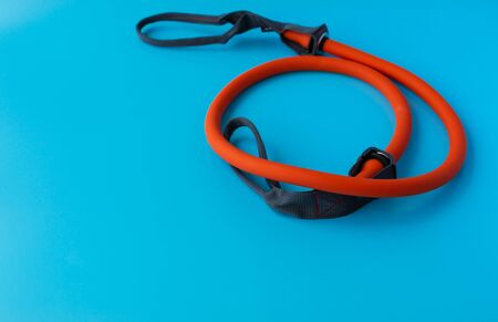 Orange Elastic Rubber Band on a Blue Background. Fit, fitness, exercise, workout and healthy lifestyle. Copy space for text