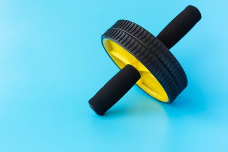 Yellow and Black Abs Roller Wheel on a Blue Background. Fitness Wheel isolated on a Blue Background. Copy Space for Text Banco de Imagens