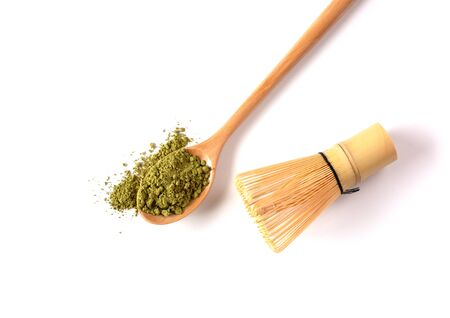 Matcha powder tea in a wooden spoon with a bamboo chasen (whisk)on a white Backgound. Japanese Culture. Tea Ceremony Concept. Copy Space