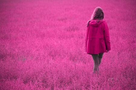 Young Woman Walking  Back on a Unusual field. Toned in Pink color with neon.Unnatural  Pink color trend concept. Banco de Imagens