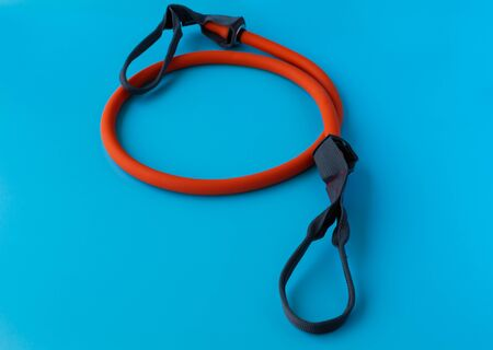Orange Elastic Rubber Band on a Blue Background. Fit, fitness, exercise, workout and healthy lifestyle.